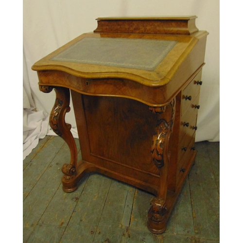 3 - A Victorian walnut Davenport of customary form with leaf carved scrolling supports and hinged cover ...