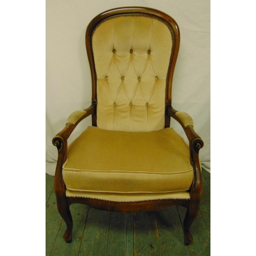 33 - A mahogany button back armchair with scrolling arms and legs...