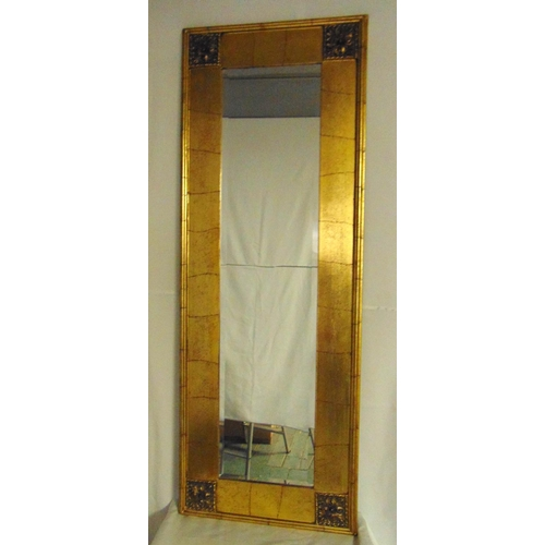 35 - A rectangular Arts and Crafts style gilded framed wall mirror, 145 x 53cm...