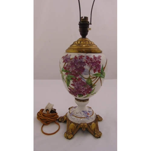 43 - A French ceramic lamp base the ovoid body decorated with flowers and leaves on four gilded metal scr...