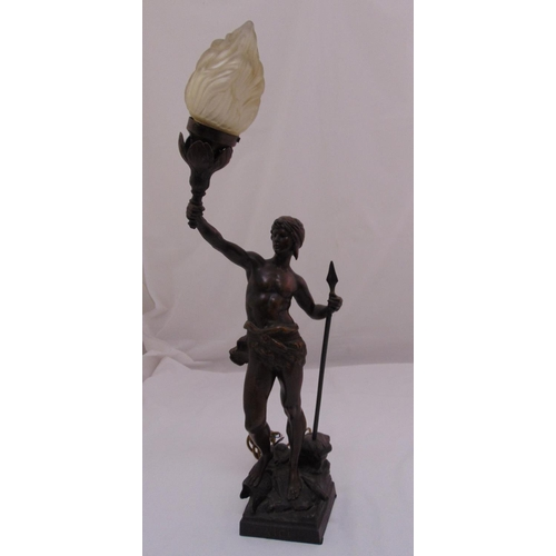 45 - A spelter lamp stand in the form of a warrior holding a spear and supporting a frosted glass flame s...