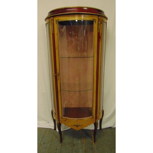 9 - A continental glazed display cabinet of cylindrical form with gilt metal mounts, hinged door on four...