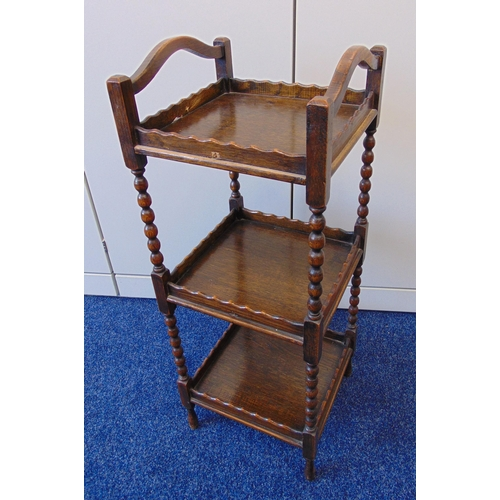 15 - An oak three tier whatnot, square form with two side handles on four tapering cylindrical legs, 76 x...