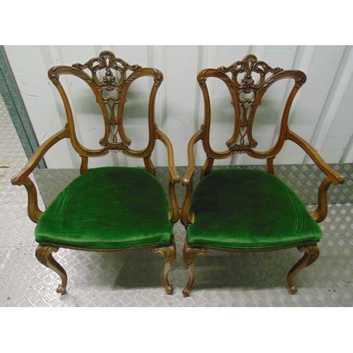 24 - A pair of Edwardian occasional armchairs with scrolling arms and scroll pierced backs on four leaf c...