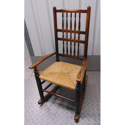 30 - A Victorian oak Cotton Mill spindle rocking chair with rush matting seat