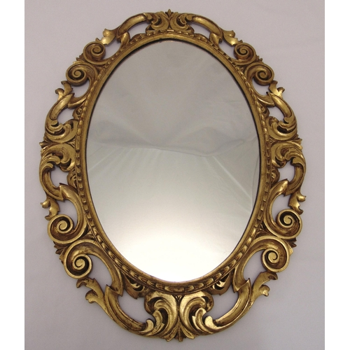 31 - An oval gilded wooden wall mirror, pierced and carved with scrolls and stylised leaves, 77 x 57.5cm