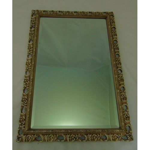 32 - A rectangular scroll pierced and stained wooden mirror with bevelled edge, 73.5 x 51cm