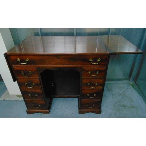 5 - A rectangular mahogany kneehole desk with drop flap to the sides, nine drawers with brass swing hand...
