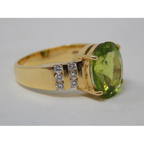 22 - Peridot & Diamond Ring. The Large Oval Peridot estimated weight 4.85cts with two rows of round brill...