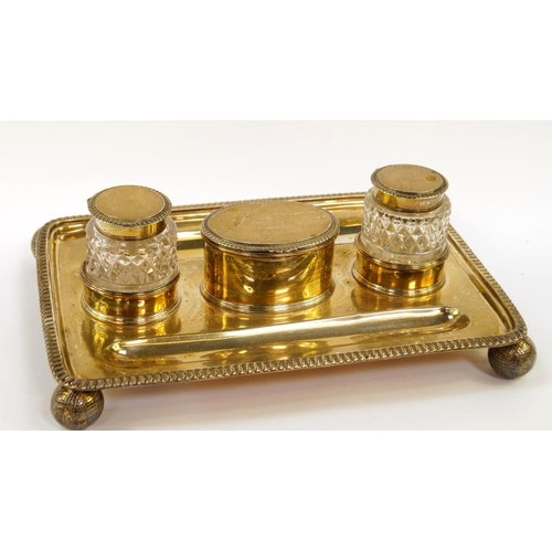 12 - An Edward VII silver desk stand, of rectangular form within gadrooned border, having two pen recesse...