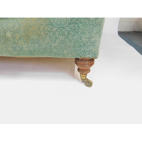 10 - A Howard & Sons three seater sofa, with scroll arms, upholstered in patterned green fabric, raised o...