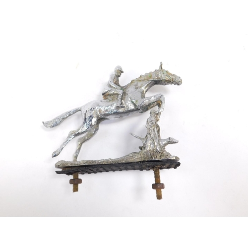3007 - A chrome plated car mascot modelled as a huntsman and horse, jumping over a fence, 11cm H....