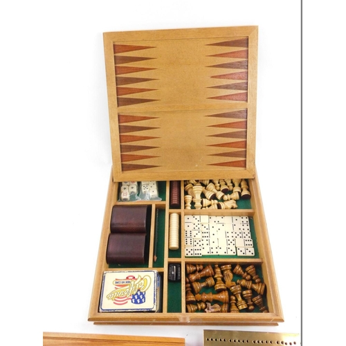 40 - A wooden cased games compendium, containing chess, dominoes, cards and poker die, the box with chess...