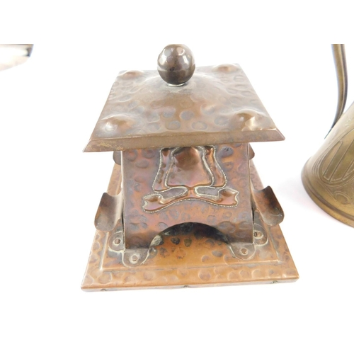 21 - An Art Nouveau copper ink well, of square section, with a hinged lid, glass well, the body embossed ...