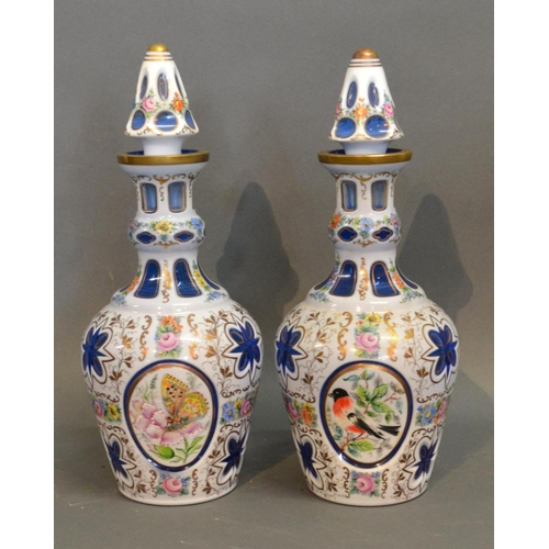 3 - A Pair Of Bohemian Cameo Glass Decanters With Stoppers decorated in polychrome enamels with reserves...