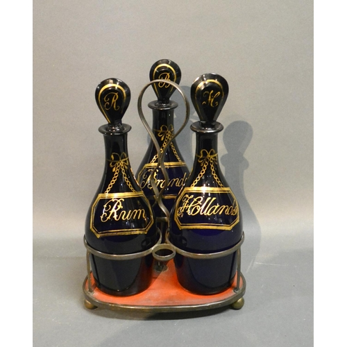 27 - A Set Of Three Regency Blue Glass Decanters With Stoppers, gilded with Rum, Brandy and Hollands comp...
