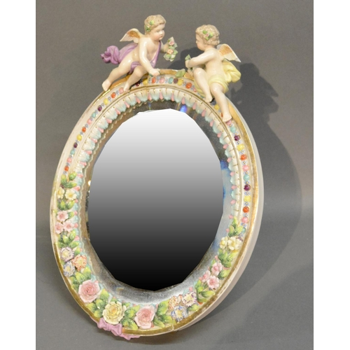36 - A German Porcelain Oval Table Mirror Surmounted With Cupid and foliate encrusted decoration, 36cm by...