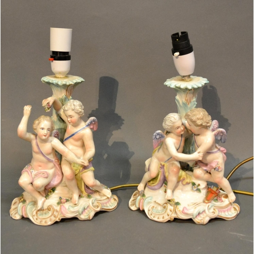 40 - A Pair Of German Porcelain Table Lamps Each Decorated With Putti upon shaped bases, 23cm tall...