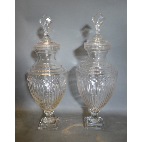 51 - A Pair of Large Cut Glass Oviform Covered Vases of Ribbed form with square stepped bases, 70cm tall
