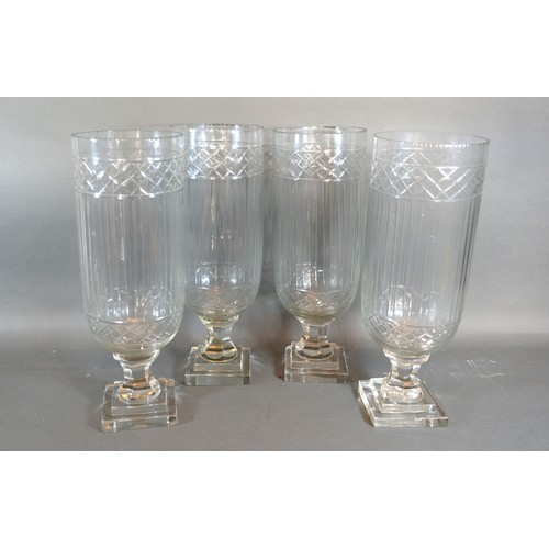 13 - A Set of Four Glass Storm Lamps with square stepped bases, 34 cms tall