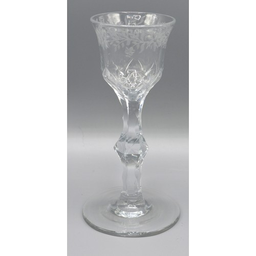 20 - A Fine Cut Stem Wine Glass engraved with flowers, 15 cms tall
