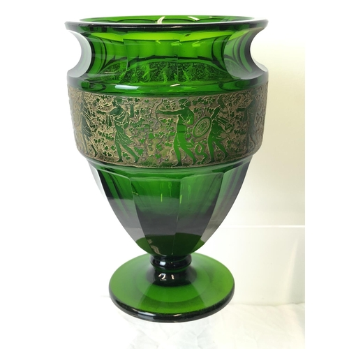 50 - Moser - An Emerald green glass facetted urn vase, decorated with a continuous oroplastic frieze of G...