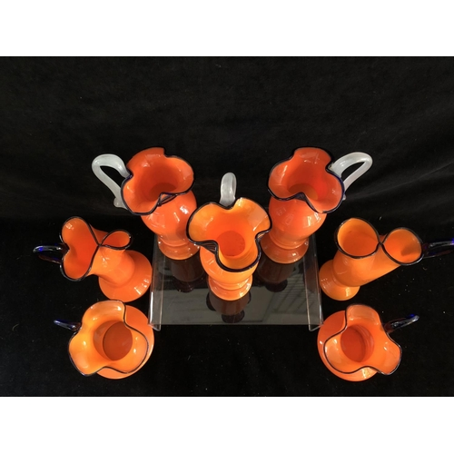58 - Tango Glass - Seven bright orange glass jugs, of various shapes, trailed in blue, 25cm high (7)...