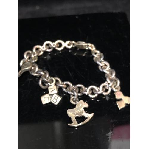 35 - Two childs silver and enamel charm bracelets, stamped 925; and one other fitted with a cross (3)...