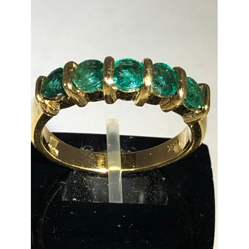 48 - An emerald half hoop ring, the five stones set  within bars in yellow metal stamped 18K, ring size O...