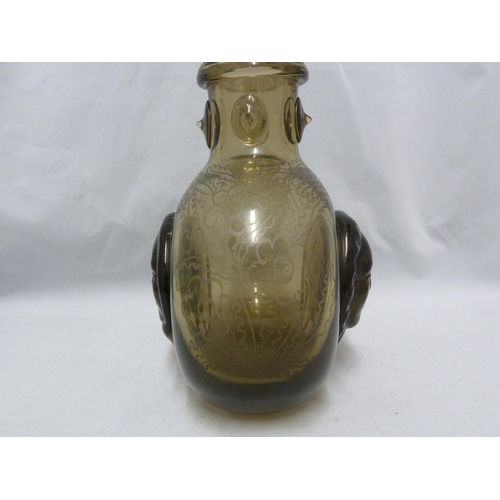 56 - Seguso - a  dark amber glass flask, the flattened globular body applied with a female head to each s...