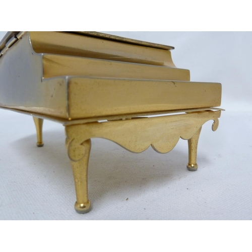 123 - A damascene musical box, in the form of a piano, the whole gilded and decorated with a reserve of Do...