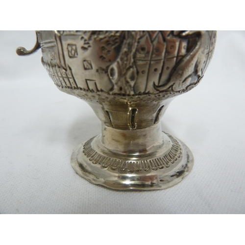 15 - A George III silver cream jug of baluster form with leaf capped scroll handle, embossed with a dog a...