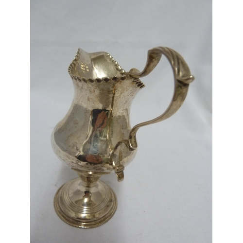 16 - A George III silver cream jug of plain baluster shape with a punch beaded rim, leaf capped double sc...