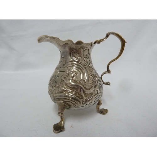 17 - A George II silver cream jug, of baluster form embossed with a bird and a dog flanking a foliate 'c'...