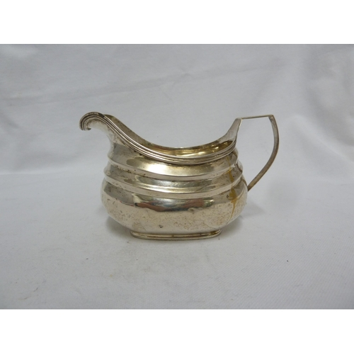19 - A George III silver cream jug, of rounded rectangular section with stepped banding and reeded rim wi...