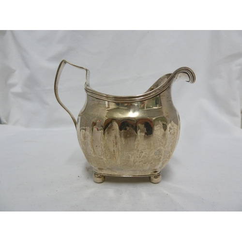 21 - A George III silver cream jug of rounded oblong bellied form with part convex fluting under a reeded...