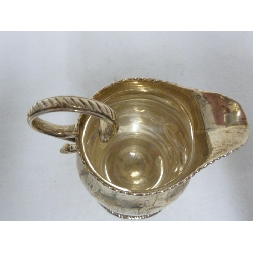 22 - A George III silver cream jug, of squat baluster form with gadrooned border and flying scroll handle...