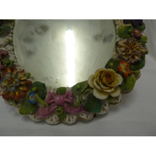 55 - A sitzendorf porcelain looking glass frame, oval decorated with applied flower garland with ribbon a...