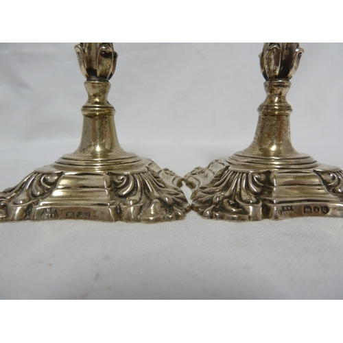 6 - A pair of Victorian silver taper sticks in George II style,  of fluted baluster stems supporting sha...