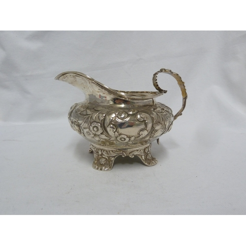 8 - A George IV silver cream jug of circular form with reeded scalloped rim and floret capped handle, th...