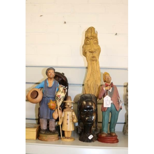 27 - A selection of wooden carved figurines together with two terracotta figures both signed....
