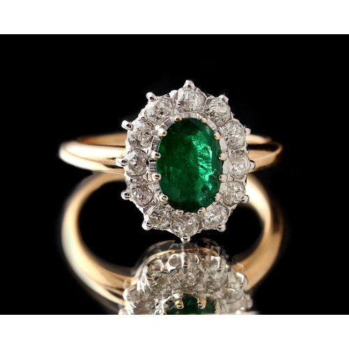 29 - An unmarked yellow gold emerald & diamond cluster ring, the oval cut emerald approximately 0.80 cara...