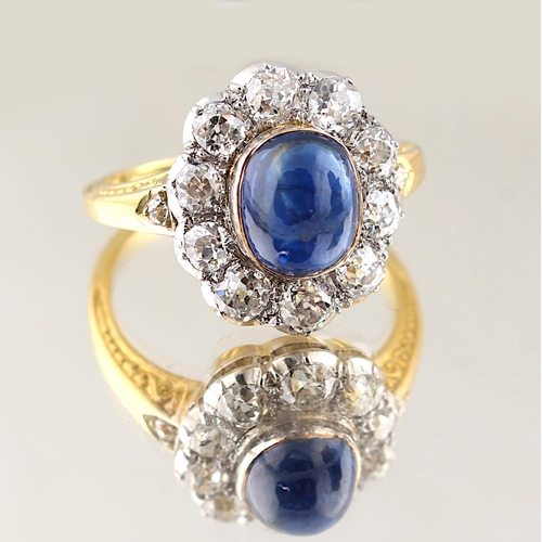 35 - A yellow gold cabochon sapphire & diamond cluster ring, the oval cabochon sapphire weighing approxim...