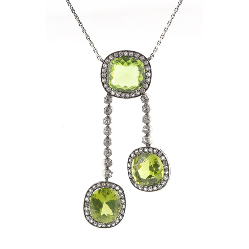 47 - A peridot & paste tassel necklace, the three cushion cut peridots weighing a total of approximately ...