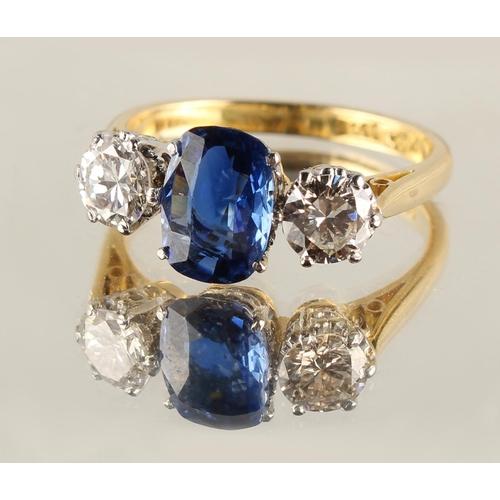 171 - An 18ct yellow gold sapphire & diamond three stone ring, the central cushion cut sapphire weighing a...