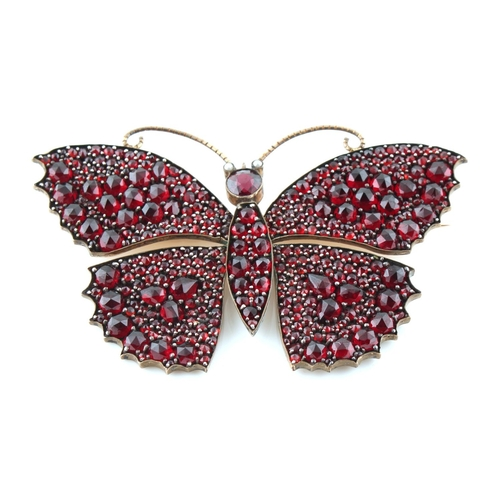 200 - A large garnet butterfly brooch, with rose cut garnets & seed pearl eyes, 78mm across, approximately...