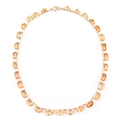 202 - A late Georgian topaz riviere necklace, the thirty graduated topaz collets weighing an estimated tot...
