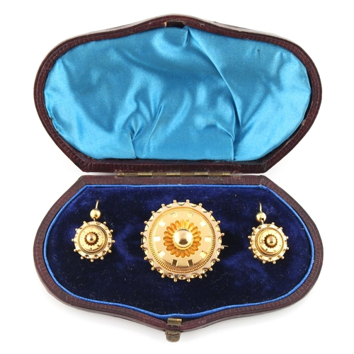 203 - A Victorian unmarked yellow metal circular brooch with earrings en suite, each with diamond registra...