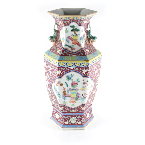259 - Property of a lady - a late 19th century Chinese ruby ground famille rose hexagonal vase, painted wi...
