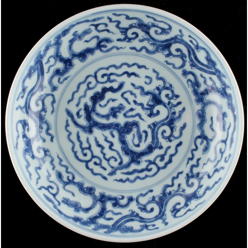 266 - A Chinese blue & white dragon dish, the base un-glazed, 8.1ins. (20.5cms.) diameter (see illustratio...